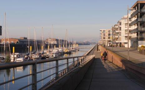 Links im Bild ist ein kleiner Yachthafen mit Booten zu sehen. Rechts davon verläuft eine Promenade, die mit Häusern bebaut ist. Radfahrer fahren die Promenade entlang.