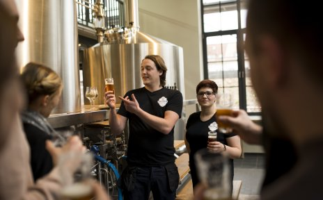 Ein Mitarbeiter und eine Mitarbeiterin der Union Brauerei führen eine Brauereiführung für Gäste durch.