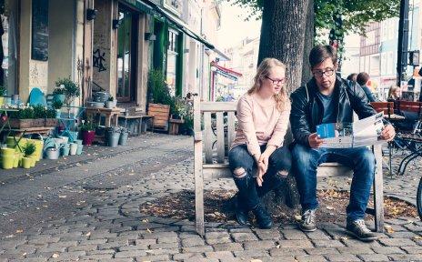 Eine Junge Frau und ein junger Mann sitzen auf einer Holzbank an einer Straße und schauen zusammen auf einen Flyer.