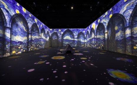 Auf die Wände des Ausstellungsraum ist ein Gemälde von Van Gogh projiziert.