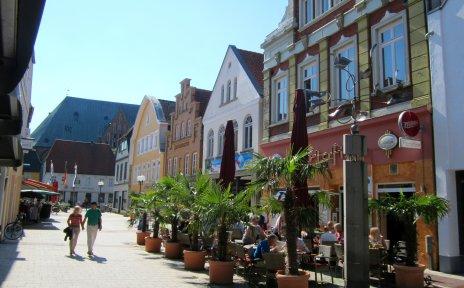 Eine Fußgängerzone mit alten Häusern an einem sonnigen Tag. Vor einem Haus befindet sich ein Straßencafé, umsäumt von Palmen.