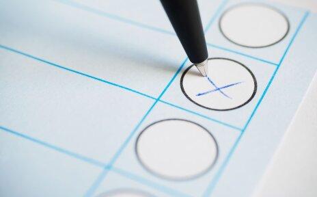 Mit einem Kugelschreiber wird ein Kreuz auf einem Wahschein gemacht.
