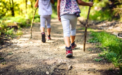 Zwei kleine Mädchen laufen mit Wanderstöcken durch einen Wald.
