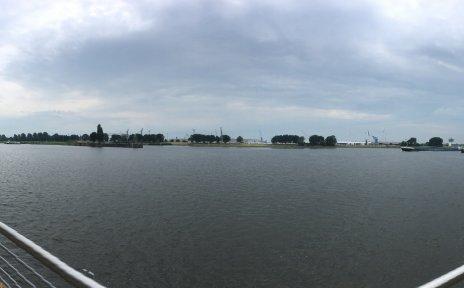Zu sehen ist eine große, dunkle Wasserfläche. Im rechten und linken Teil des Bildes ist ein Metallgeländer zu erkennen. Links legt ein Boot an.