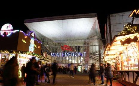 Es ist dunkel und weihnachtliche Buden mit Lichtern stehen vor dem Eingang eines Einkaufscenters.