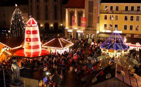 Ein Weihnachtsmarkt mit beleuchteten Buden und vielen Menschen aus der Vogelperspektive.