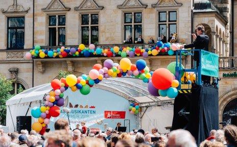 Die Bremer Philharmoniker auf einem Balkon und musizieren. Das Gebäude ist mit bunten Luftballons geschmückt. Marko Letonja dirigiert im Vordergrund.