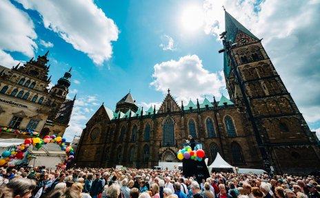 Eine Menschenmenge steht auf dem Domshof, der Bremer Dom ragt über sie hinaus.