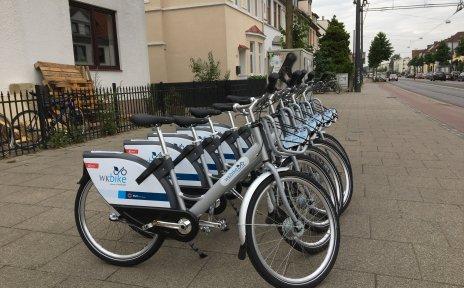 Mehrere Wk-Bikes stehen aufgereiht auf dem Fußweg.