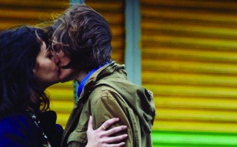Zwei Personen stehen vor einer gelben Wand und küssen sich; Quelle: quueerfilm festival