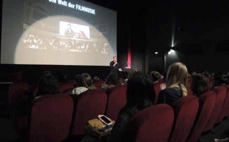 Zu sehen ist ein Kinosaal. Eine Person steht mit einem Mikrofon auf der Bühne und erklärt etwas