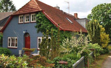 Ein blaues Wohnhaus mit rot-braunen Ziegeln, umgeben von Garten.