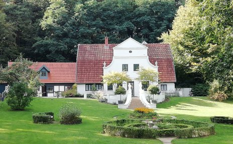 Ein großer, aufwendig angelegter grüner Garten. Im Hintergrund ist ein weißes Haus im Jugendstil zu sehen, der Barkenhoff in Worpswede.