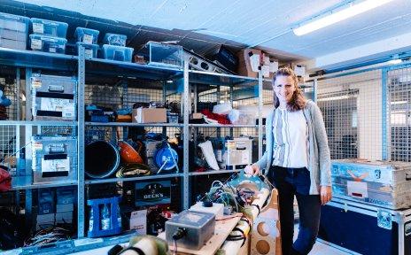 Frau Arndt steht in einem Lagerraum und hält sich an einer Maschine fest