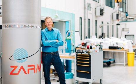 Ein Mann steht an einer Säule angelehnt in einem Labor