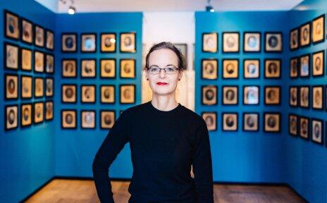 Eine Frau vor einer Bilderwand im Museum