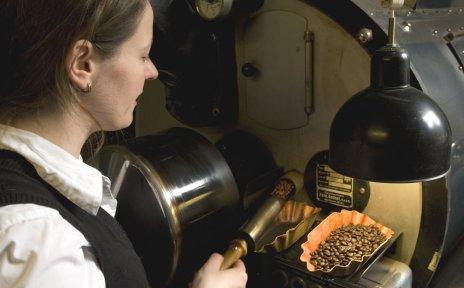 Eine Frau nimmt Kaffeebohnen aus einer großen Maschine.