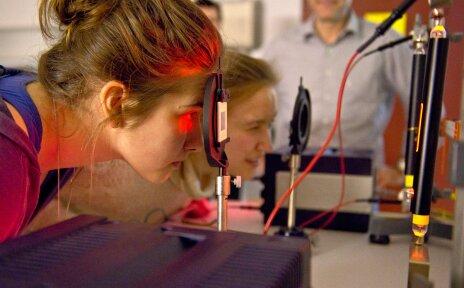Zwei rot angeleuchtete Mädchen schauen durch einen aufgestellten Objektträger