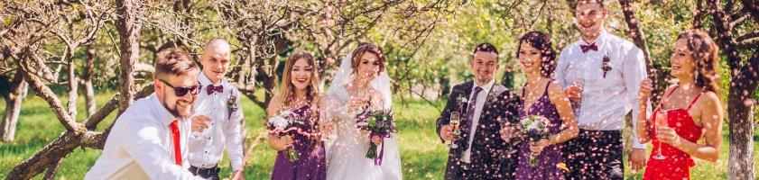 Ein Brautpaar steht mit seinen Gästen auf dem Rasen und lässt Konfetti regnen