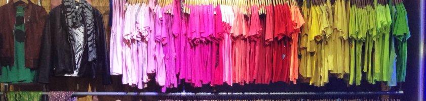 Bunte T-Shirts auf mehreren Kleiderstangen gestapelt