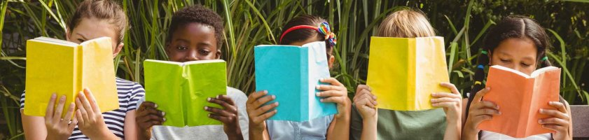 5 lesende Kinder auf einer Bank im Grünen