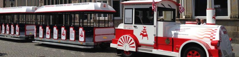 Eine weiß-rote Lokomotive, die auf dem Marktplatz steht.