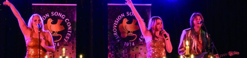 Auf dem Foto sind die Darsteller von ABBA abgebildet. Stilecht tragen sie goldene Kleidung und heizen den Zuschauern auf der Bühne ordentlich ein.