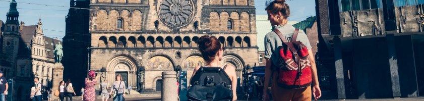 Zwei Frauen auf dem Bremer Marktplatz. Sie blicken auf den Dom und unterhalten sich. Eine von ihnen sitzt im Rollstuhl.