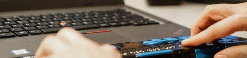 Ein Laptop mit Braillezeile, Hände ertasten den Text in Blindenschrift.