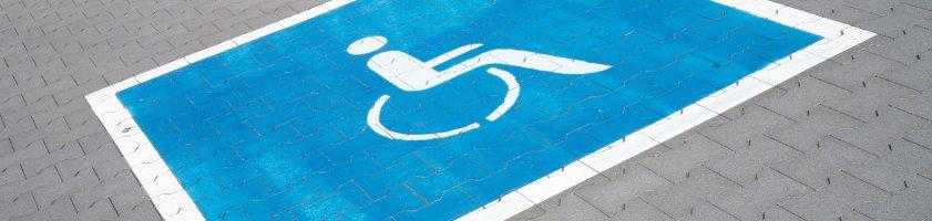 Ein aufgemaltes Rollstuhl-Symbol auf einem Behindertenparkplatz.