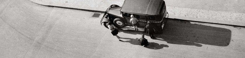 """Ein Schwarz-Weiß-Foto von Eva Besnyö. Es zeigt eine Luftansicht auf eine Straßenecke. Zu sehen ist ein Auto und wenige Menschen, ein Laden mit der Aufschrift """"Bäckerei, Konditorei, Café"""" und eine Litfasssäule."""