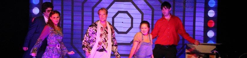 """Auf dem Foto sind die Schauspieler des Theaterschiffs abgebildet, die in ihren Rollen für die Parodie der """"Hitparade"""" auf der Bühne stehen."""