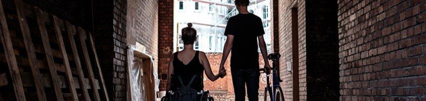 Eine junge Frau im Rollstuhl und ein junger Mann, der ein Fahrrad schiebt, halten sich an der Hand (Quelle: Andi Weiland | Gesellschaftsbilder.de).