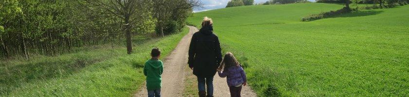 Eine Frau geht mit zwei Kindern auf einem Weg spazieren, links und rechts grüne Wiese und Bäume (Foto: privat/barckhausen).