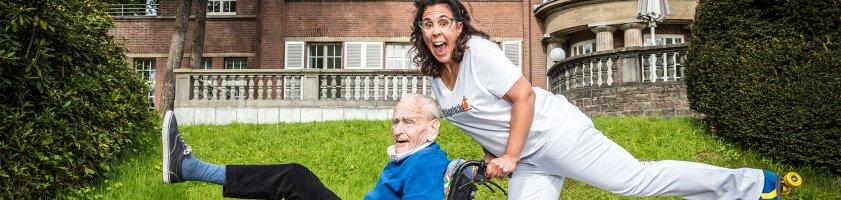 Frau in Rollschuhen schiebt älteren Mann im Rollstuhl, beide heben ein Bein in die Höhe