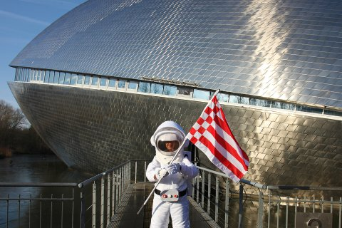 Eine Person in einem Astronauten Kostüm steht vor dem Universum Bremen und hält die rot weiße Speckflagge in den Händen.