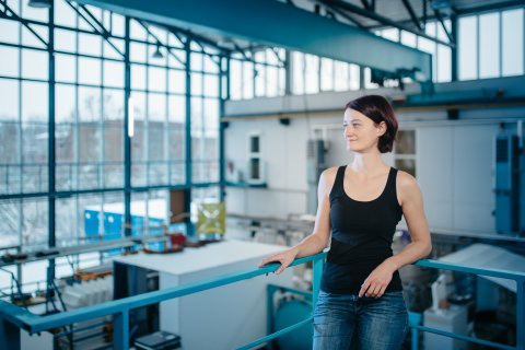 Eine Frau lehnt an einem Geländer und steht oberhalb einer Halle.