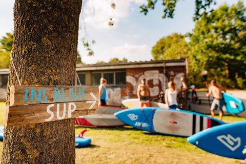 Im Vordergrund ist ein kleiner Wegweiser mit der Aufschrift der SUP Schule Ins Blaue. Im Hintergrund sind Personen verschwommen abgebildet.