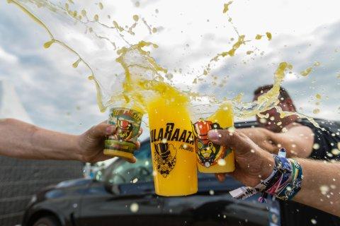Gäste des Tabularaaza Festivals stoßen mit Festival Bechern an. Bei dem Getränk in der Mitte schwappt eine gelbe Flüssigkeit über.