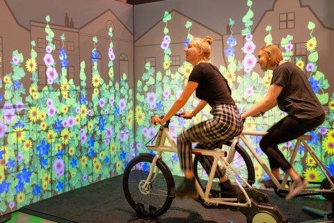 Zwei Mädchen, die auf Fahrrädern sitzen, und sich eine virtuelle Blumenlandschaft auf einer Leinwand anschauen.