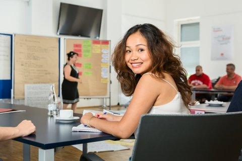 Eine junge Frau dreht sich zur Kamera. Sie sitzt in einem Kursraum, der im Hintergrund verschwommen zu sehen ist.
