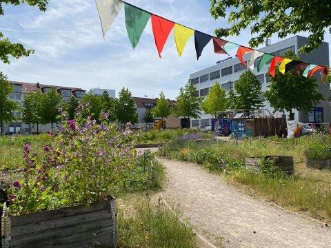 Ein Rundumblick über das Gelände eines öffentlichen Gartens in der Stadt. Eine Girlande flattert im Wind.