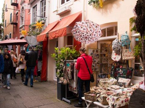 Ein Souvenier-Geschäft mit bedruckten Taschen und eine Frau wählt gerade etwas aus.