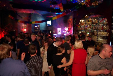 Viele Menschen feiern in einem Partyraum Silvester. Es ist geschmückt mit bunten Girlanden.