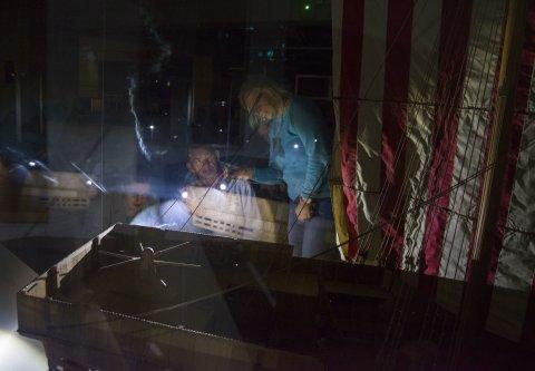 Zwei Personen mit Taschenlampen im Dunkeln in einem Museum