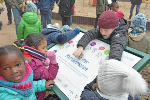 Kinder entdecken die Schautafel zu Kinderrechten.