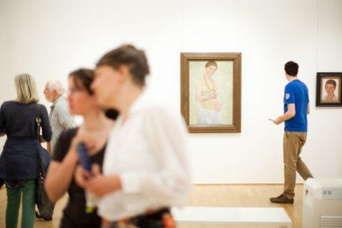 Besucher im Museum schauen sich Gemälde an.