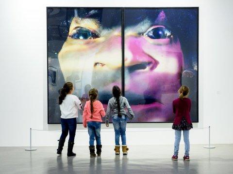 Vier junge Mädchen stehen vor einem bunten Bild mit einem verzerrten Gesicht.
