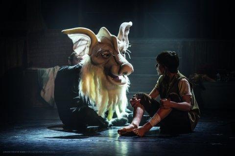 Der Glücksdrache Fuchur und ein Junge schauen sich an. Sie sind beide auf der Bühne und das Licht scheint auf sie.