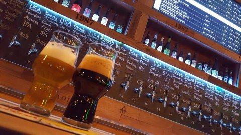 Je ein Glas mit hellem und dunklem Bier auf einer Theke vor zahlreichen Zapfhähnen